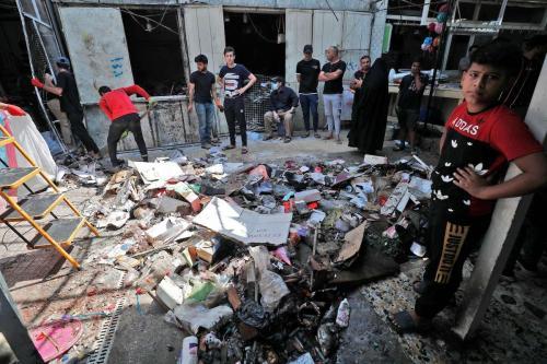 Os iraquianos inspecionam o local da explosão um dia antes em um mercado popular no leste da capital Bagdá, em 20 de julho de 2021 [Ahmad Al-Rubaye/AFP via Getty Images]