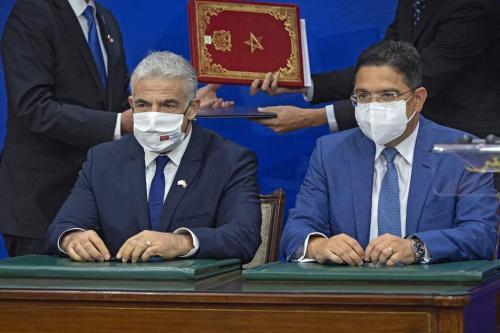 O ministro das Relações Exteriores marroquino, Nasser Bourita (dir.), senta-se próximo ao seu homólogo israelense, Yair Lapid, após assinar documentos, em Rabat, em 11 de agosto de 2021 [Fadel Senna/AFP via Getty Images]