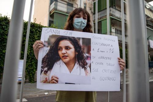 Uma mulher mostra uma fotografia de Sanaa Seif durante uma manifestação em solidariedade a Patrick Zaki e ativistas de direitos humanos detidos em todo o mundo, em 16 de junho de 2021, em Nápoles, Itália [Ivan Romano/Getty Images]