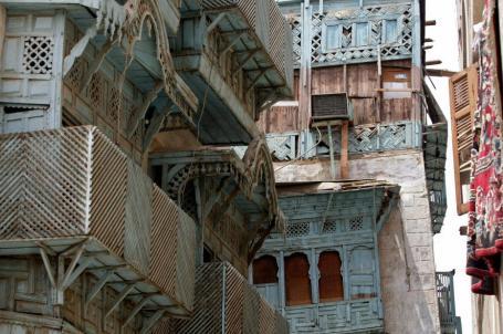 """Uma vista mostra os painéis de madeira esculpida que decoram as fachadas dos edifícios tradicionais da Cidade Velha, no centro da cidade portuária de Jeddah, na Arábia Saudita, no Mar Vermelho, em 2 de agosto de 2007. A arquitetura tradicional da Cidade Velha de Jeddah foi tipicamente construída com uma pedra chamada 'Manqabi', proveniente de vários locais, como o Lago AL-Arbain. O processo de construção envolveu colocar as pedras em fileiras conhecidas como 'Madamik' separadas por cruzamentos de madeira denominados 'Takail', que foram usados para distribuir a carga nas paredes igualmente. As portas e fachadas de muitas dessas casas tradicionais foram embelezadas com esculturas de pedra decorativas e varandas com painéis de madeira e """"quiosques"""" [Hassan Ammar/AFP via Getty Images]"""