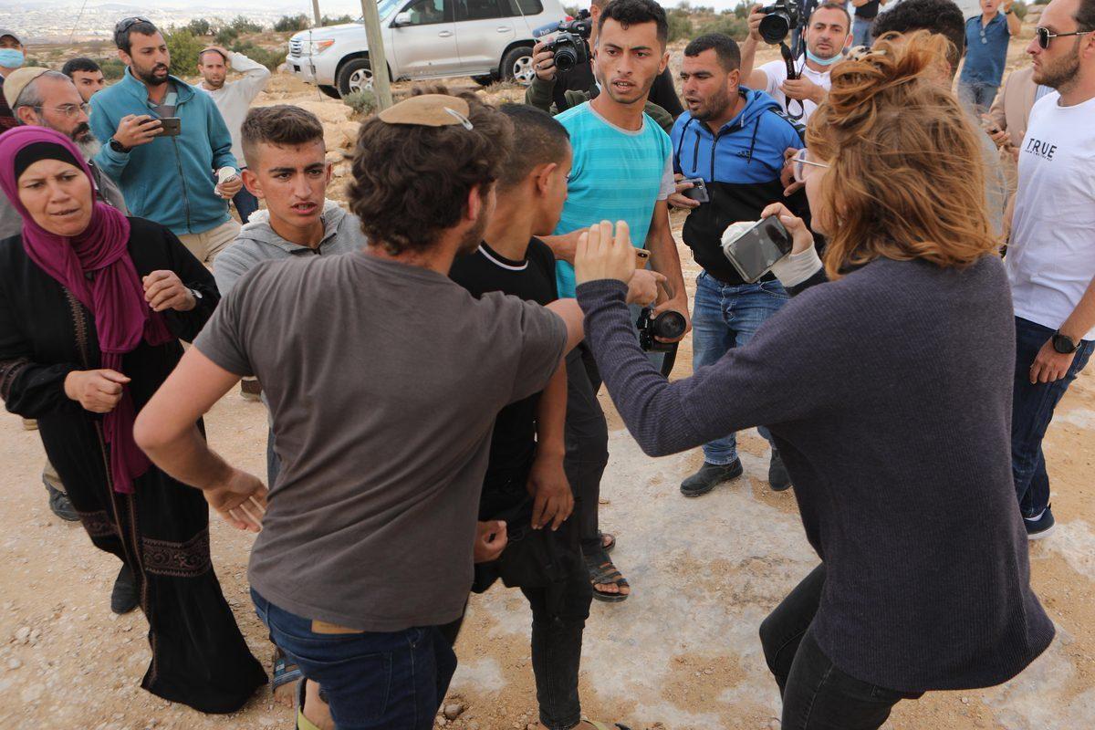 Colonos judeus atacam palestinos com paus de madeira e pedras durante a visita de embaixadores de países europeus ao distrito, na aldeia Susiya em Hebron, Cisjordânia, em 24 de setembro de 2021 [Mamoun Wazwaz/Agência Anadolu]