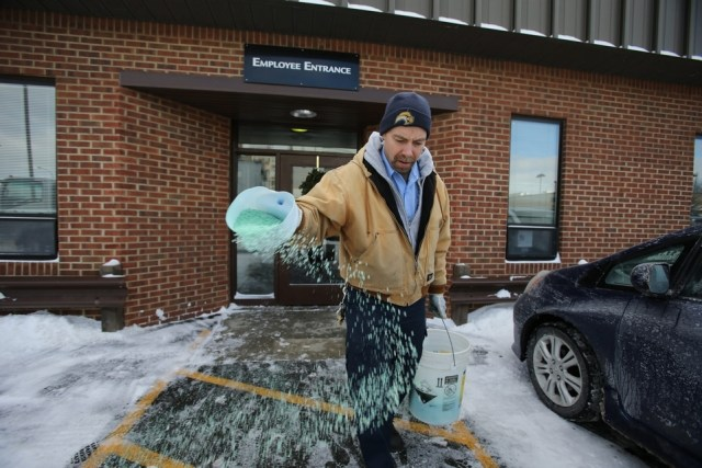 Doug Allen spreading salt to melt ice at the City Mission