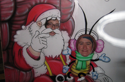 Erin the baby bee sits on Santa Janel's lap