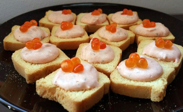 Salmon pate on small toasts topped with roe
