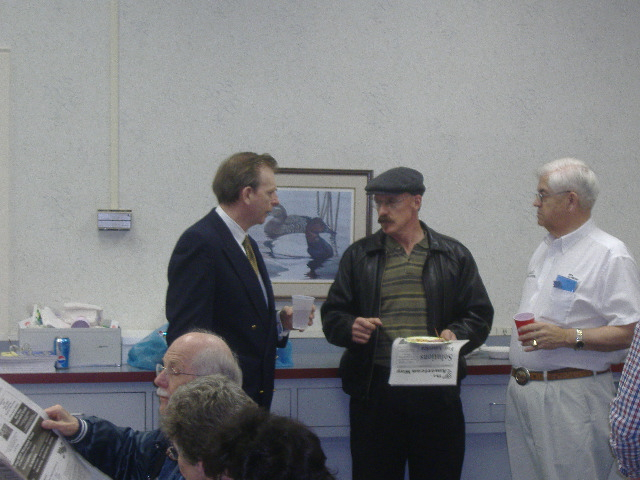 Joe Arminio discusses issues with one of his supporters. In the foreground is a gentleman reading one of his newspapers.