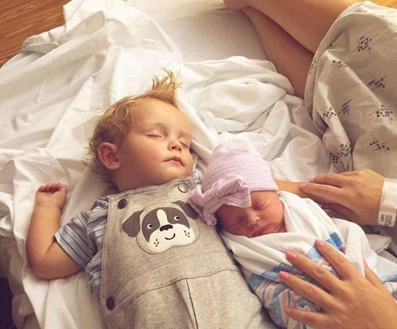 Carson and Brooklyn sleep together next to their mother on the hospital bed