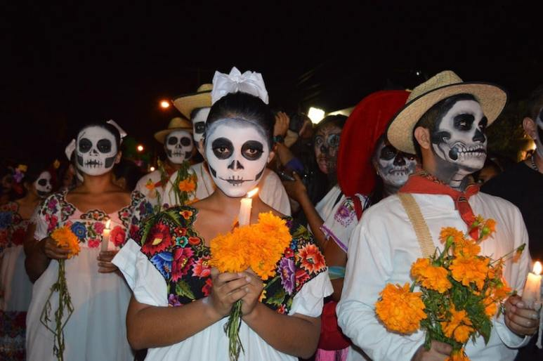 People celebrating Day of the Dead in Mexico with traditional skull mask face-paint