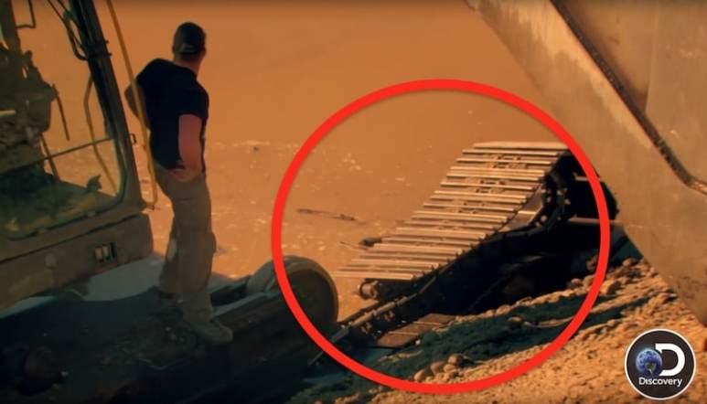 Schnabel's excavator with its track completely snapped off as Brennan surveys the damage