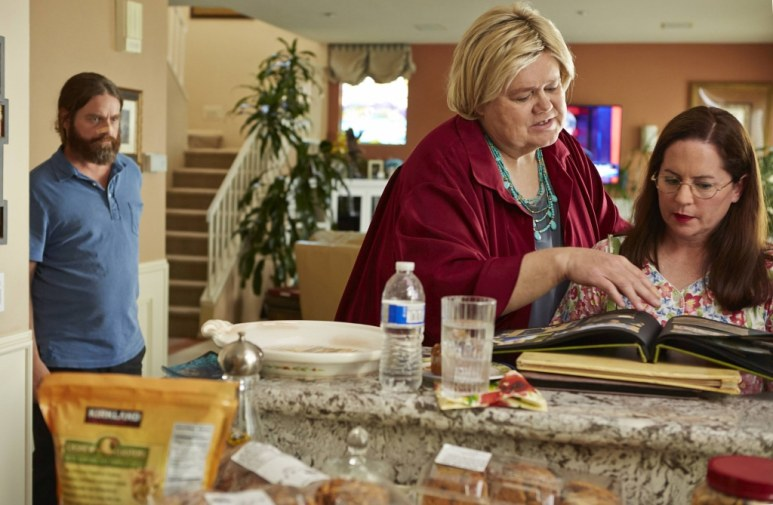 Martha Kelly as Martha, right, looks at photos with Louie Anderson's Christine and, left, Zach Galifianakis as Chip