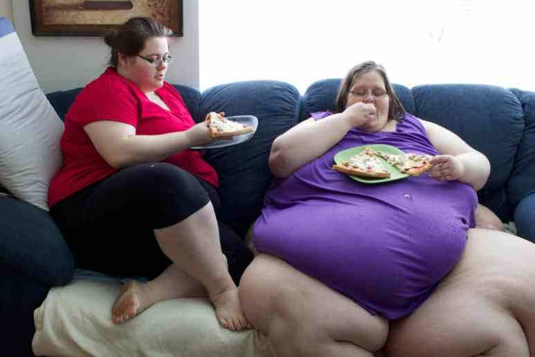 Charity and her daughter eating pizza on a couch
