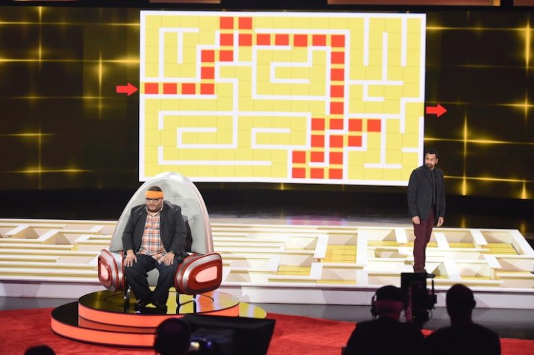David Millar guides Kal Penn around a maze while facing away from it