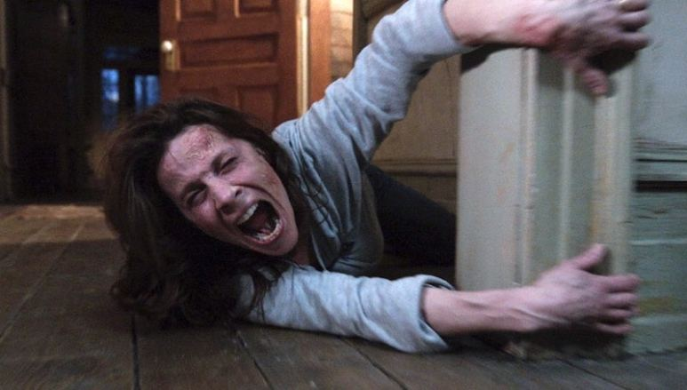 Lili Taylor as Carolyn Perron screaming as she's dragged along the floor in a scene from The Conjuring