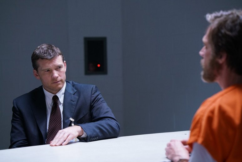 Sam Worthington as Jim Fitzgerald, sitting across a table from Paul Bettany's Kaczynski