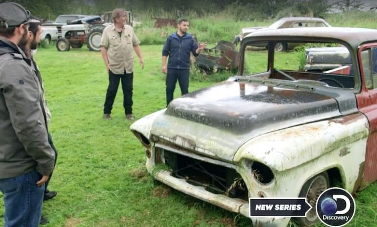 Carlos and others stand around an old GMC big-window truck in a field on Carspotting