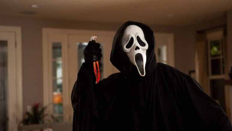 A masked figure holding a bloodied blade in Scream