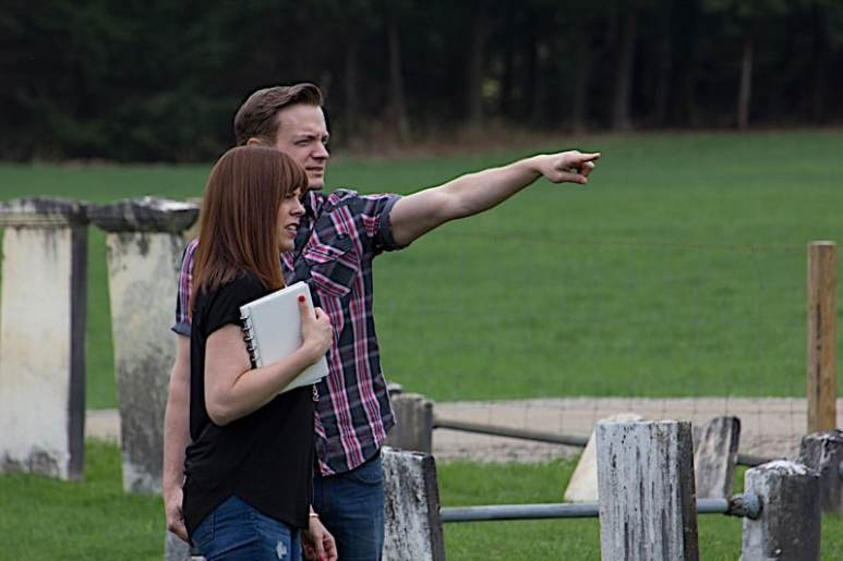 Adam Berry points out something to Amy Bruni in a cemetery.