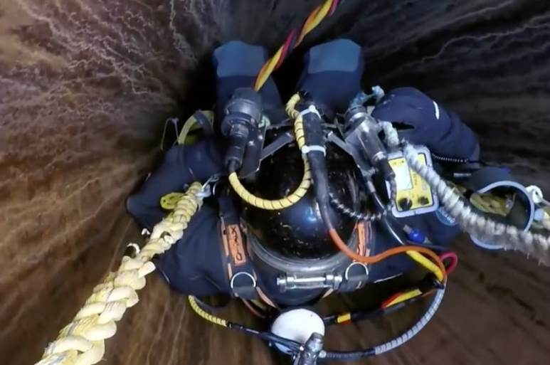 Diver being lowered down a shaft