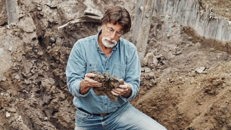 Rick examines an object inside a hole in The Curse of Oak Island Season 5