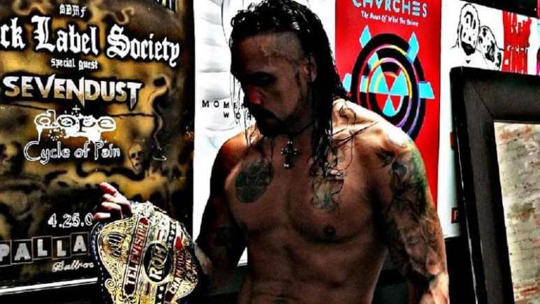 Punishment Martinez holding a title belt