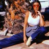 Kourtney Kardashian posing curbside in a white sports bra and blue pants