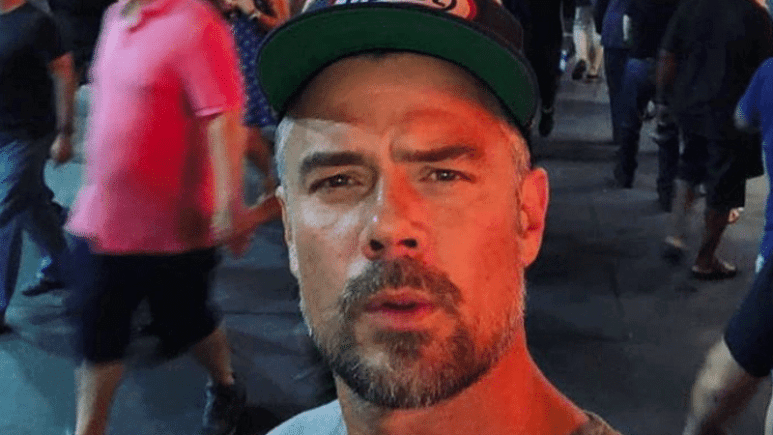 Josh Duhamel takes a selfie while surrounded by people