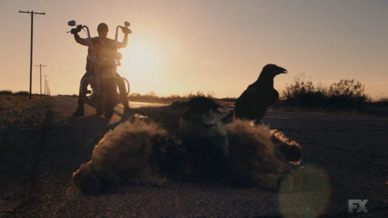 Still Image from Mayans M.C. Cuervo/Tz'ikb'uul. The opening shot shows the reverse of the opening scene of the premiere episode as three crows eat the deceased dog on the roadside. Pic Credit: FX