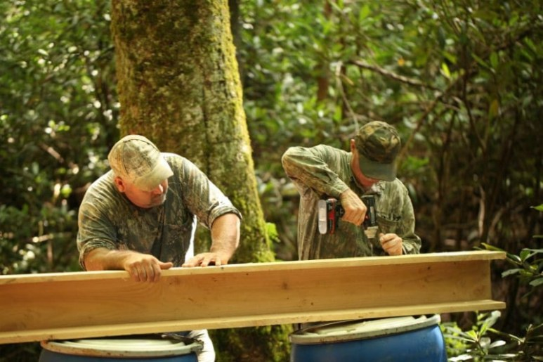 Mark and Huck creating handmade troughs to connect to the natural birch tree troughs in order to get the water where they need it.