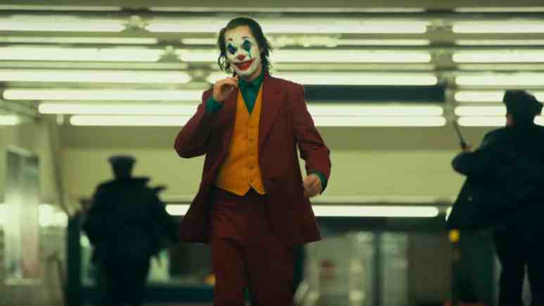 Joaquin Phoenix walking through subway in full Joker makeup.
