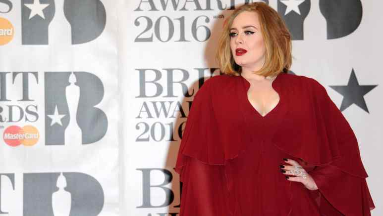 Adele poses in red gown at the 2016 Brit Awards