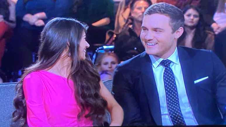 On The Bachelor Season 24 finale, Madison and Peter smile at one another on a couch in the studio.