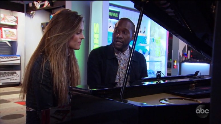 Bri and Chris sing together while sitting at a piano