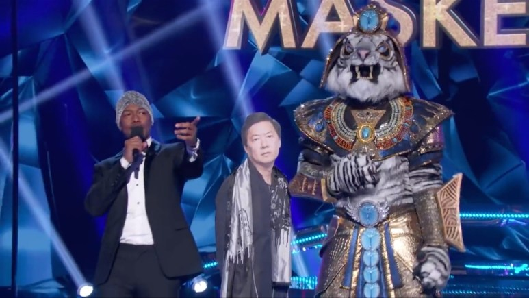 The White Tiger shows off his height compared to panelist Ken Jeong as Nick Cannon hosts on The Masked Singer. Pic credit: FOX