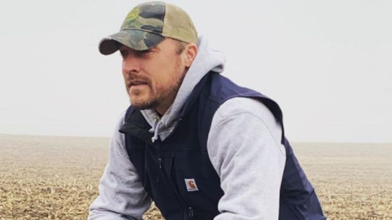 Chris Soules kneels on a farm in front of foggy weather in a baseball hat and black vest