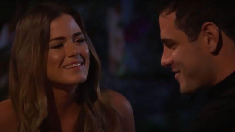 Jojo Fletcher smiles at Ben Higgins in a dark, candle lit setting