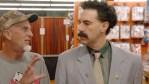 Sacha Baron Cohen as Borat talking to stranger.