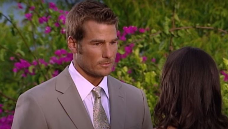 Brad Womack standing in a tan suit looking at DeAnna Pappas