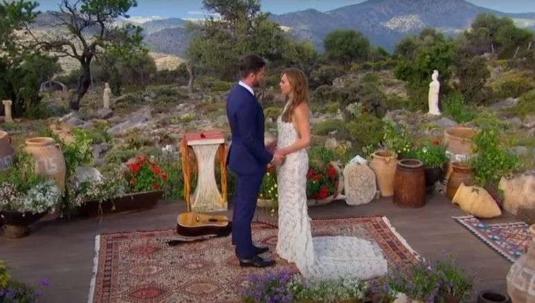 Hannah Brown in a long white dress standing in front of Jed Wyatt in a suit during their engagement