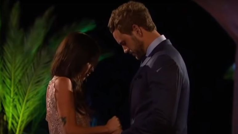 Kaitlyn Bristowe in a gold dress standing in front of Nick Viall in a suit