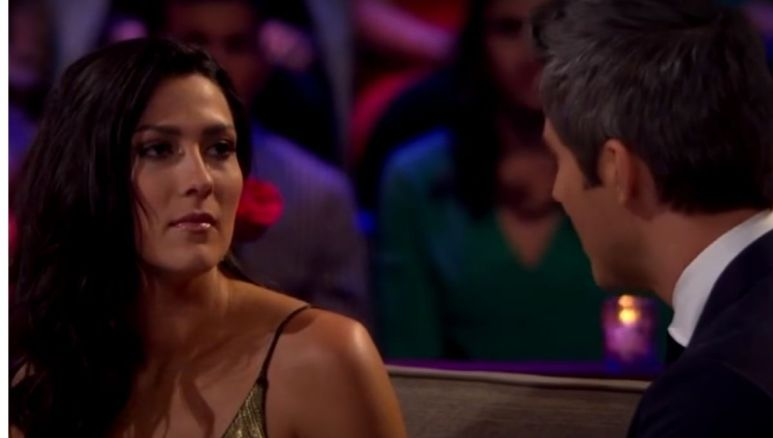 Becca Kufrin in a gold dress and the back of Arie Luyendyk Jr.'s head