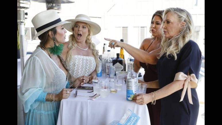 Kelly Dodd, Gina Kirschenheiter, Emily Simpson and Shannon Beador stand around a white table.