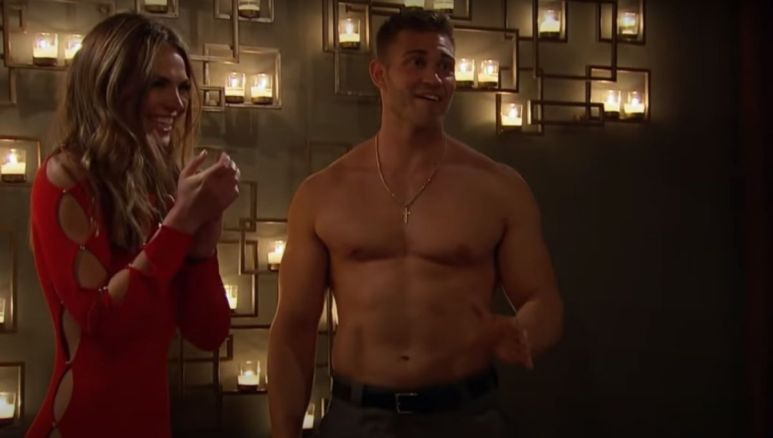 Hannah Brown smiling in a red dress while Luke Parker stands next to her without a shirt