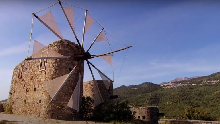 A windmill in front of a mountain view