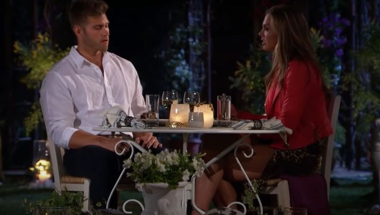 Luke Parker and Hannah Brown sit outside at a table at night