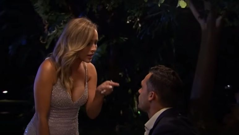 Clare Crawley in a white dress pointing her finger at Yosef Aborady as she stands over him