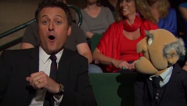 Chris Harrison making a surprised face while sitting next to an old man puppet in an audience