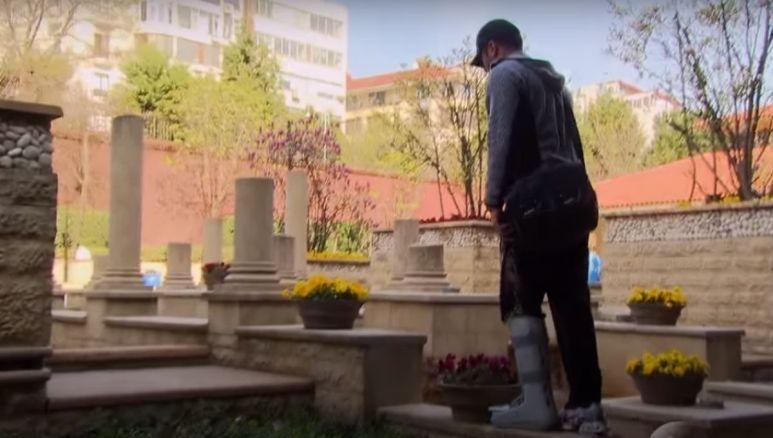 Justin Rego runs through bushes in a full leg cast