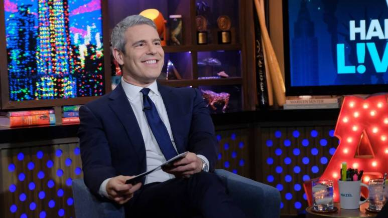 Andy Cohen sits in an armchair was he films WWHL.