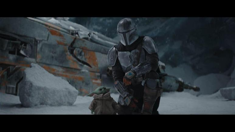 The Mandalorian knees in the snow next to Grogu with his ship in the background
