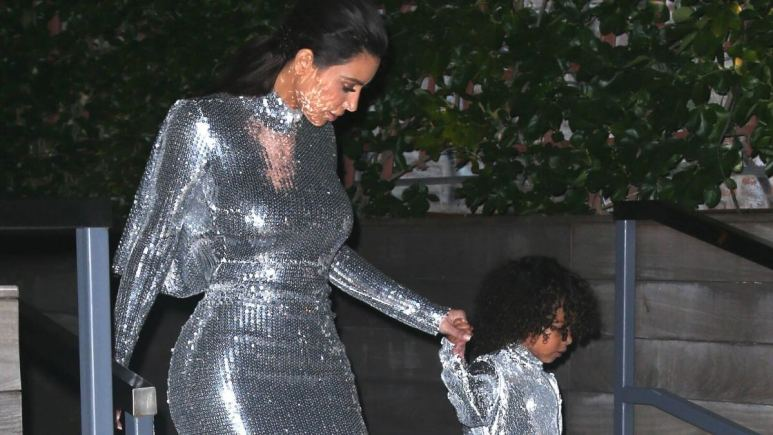 Kim Kardashian and daughter North West holding hands, walking down stairs