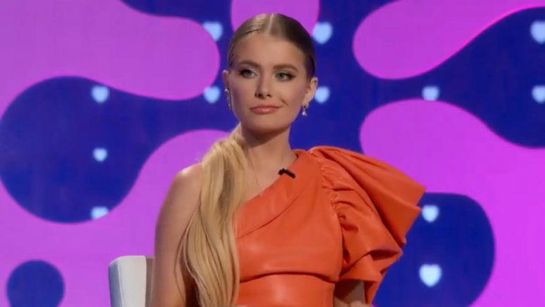 Demi Burnett grimaces in an orange dress